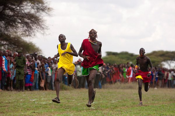 three runners in traditional clothing compete in the Maasai Olympics