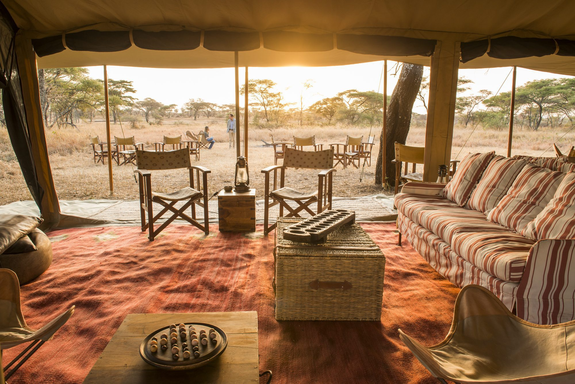 view from the inside of a tented safari camp at sunset