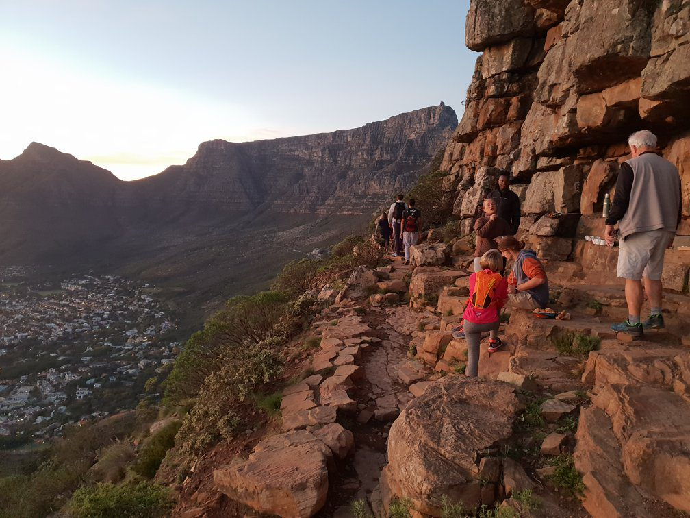 people hiking along the side of a mountain enjoying a break to look at the scenery