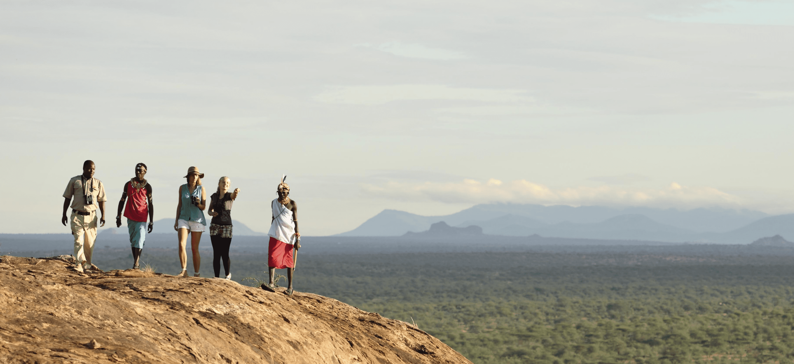 4 tourist and their guide wearing traditional samburu garbs are hiking a mountain in Samburu