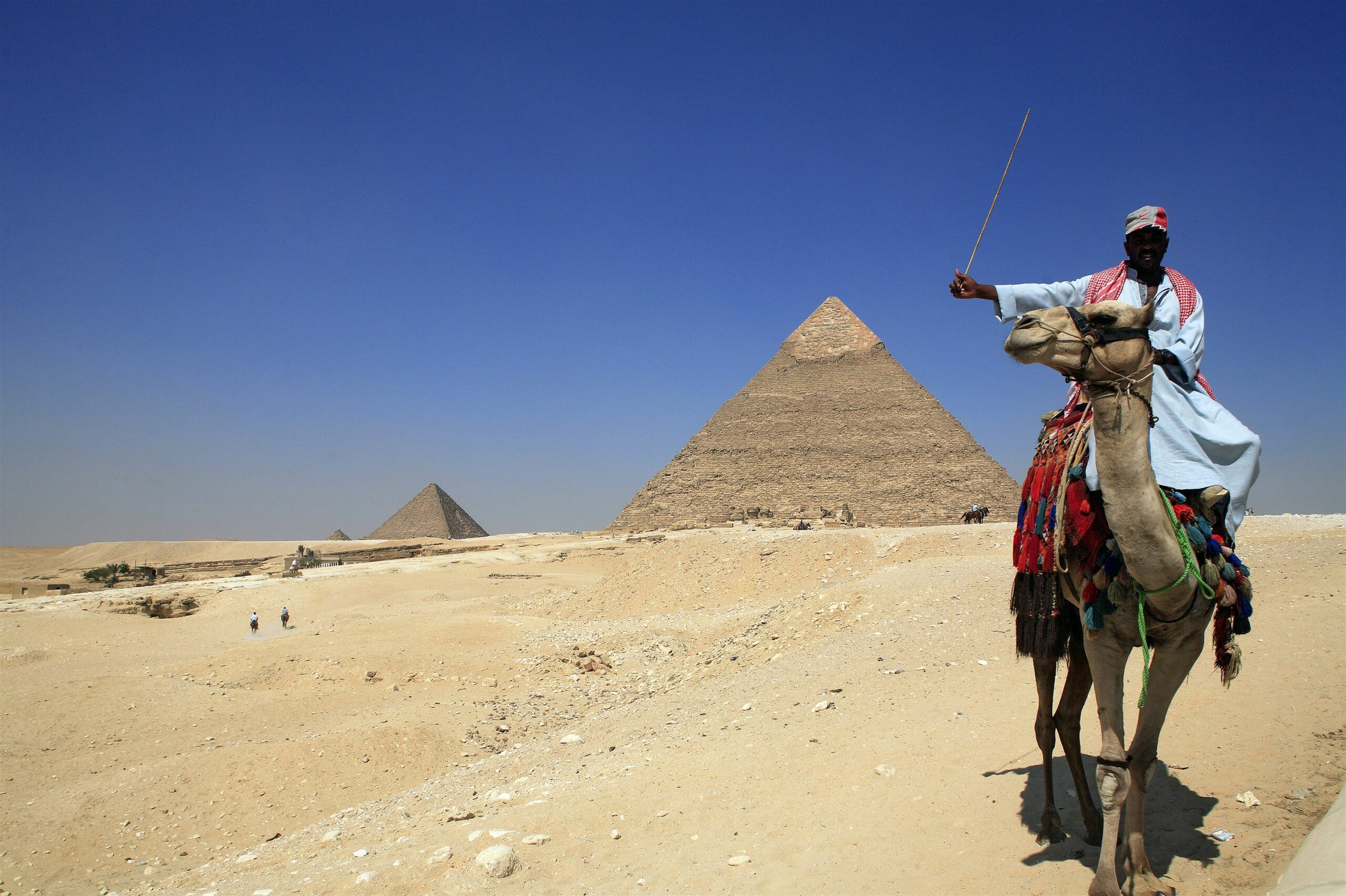 Great pyramids in background and Egyptian man on camel in foreground seen on Egypt safari