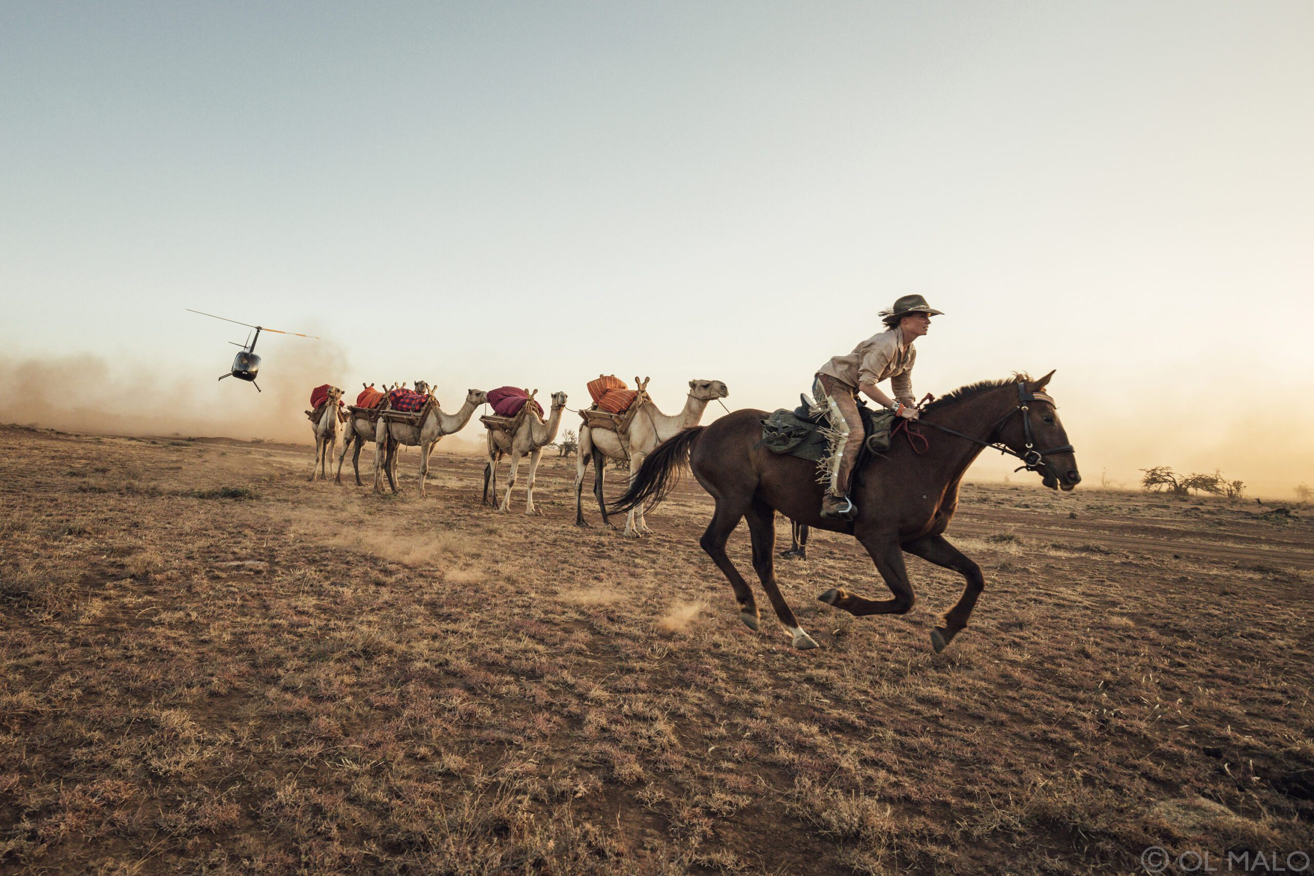 riders on horseback running across an open dirt field with a helicopter in the distance