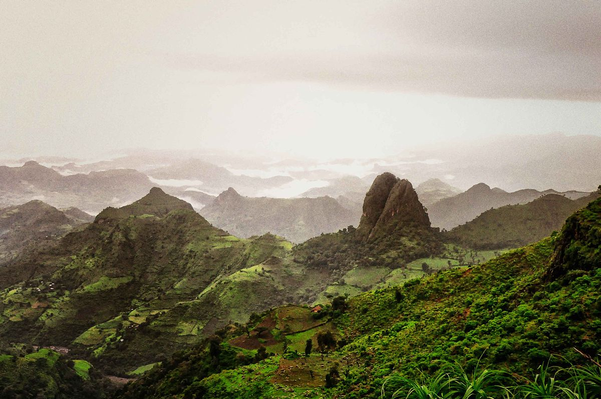 rolling picturesque view of the simien mountain range among lush green hills and fog in the background