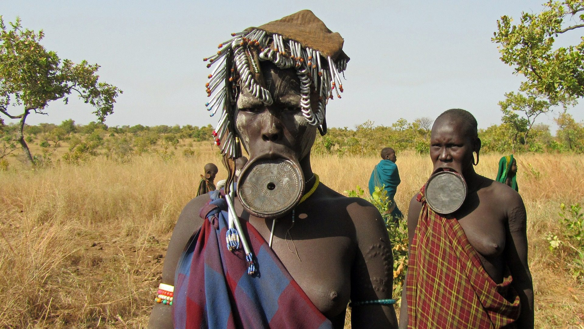 two mursi people with large lip plates dressed and adorned in their authentic tribal wear in the omo valley seen on safari in Ethiopia