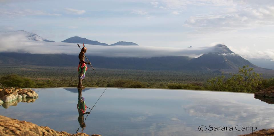 tribesman standing on the edge of the infinity pool overlooking the hills