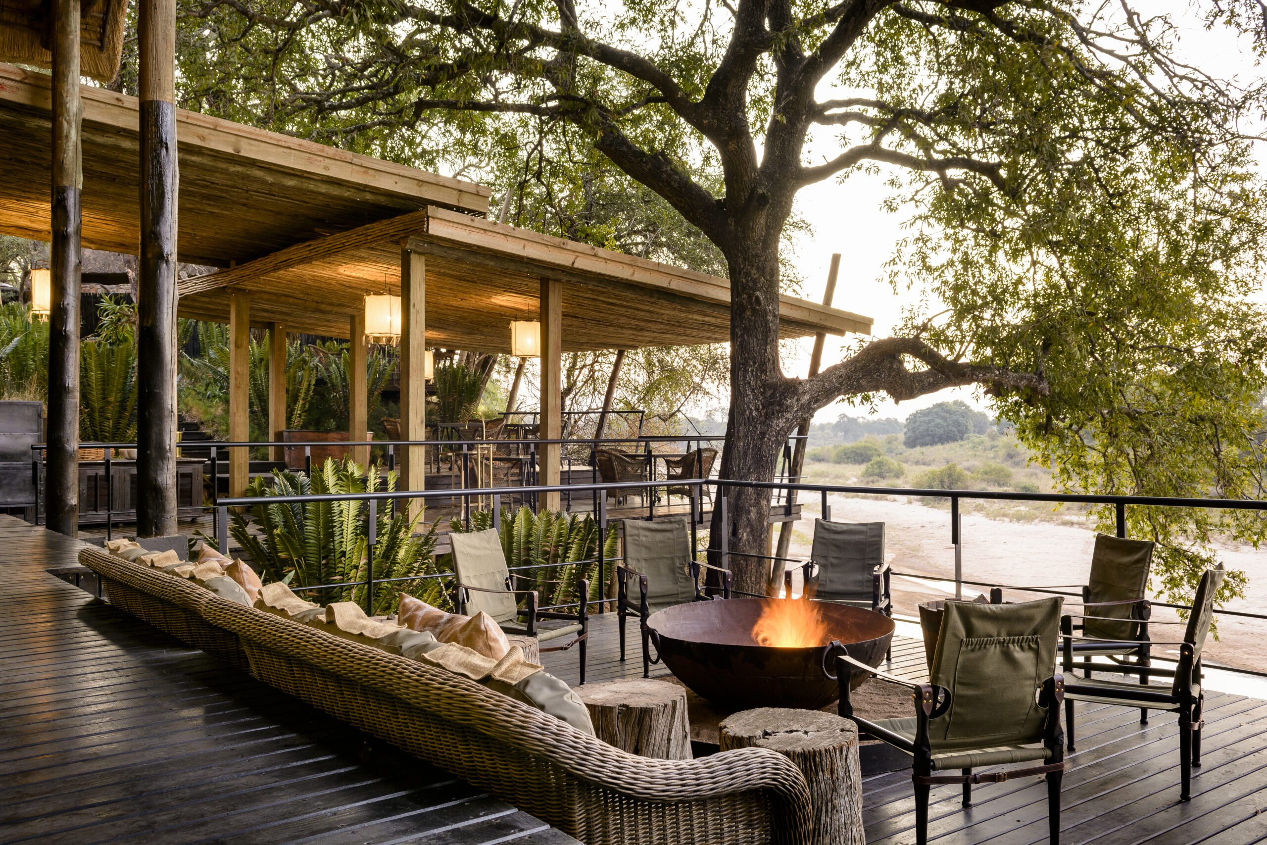 main lodge deck at Singita Ebony with a crackling fire overlooking the river in sabi sands on a South Africa safari