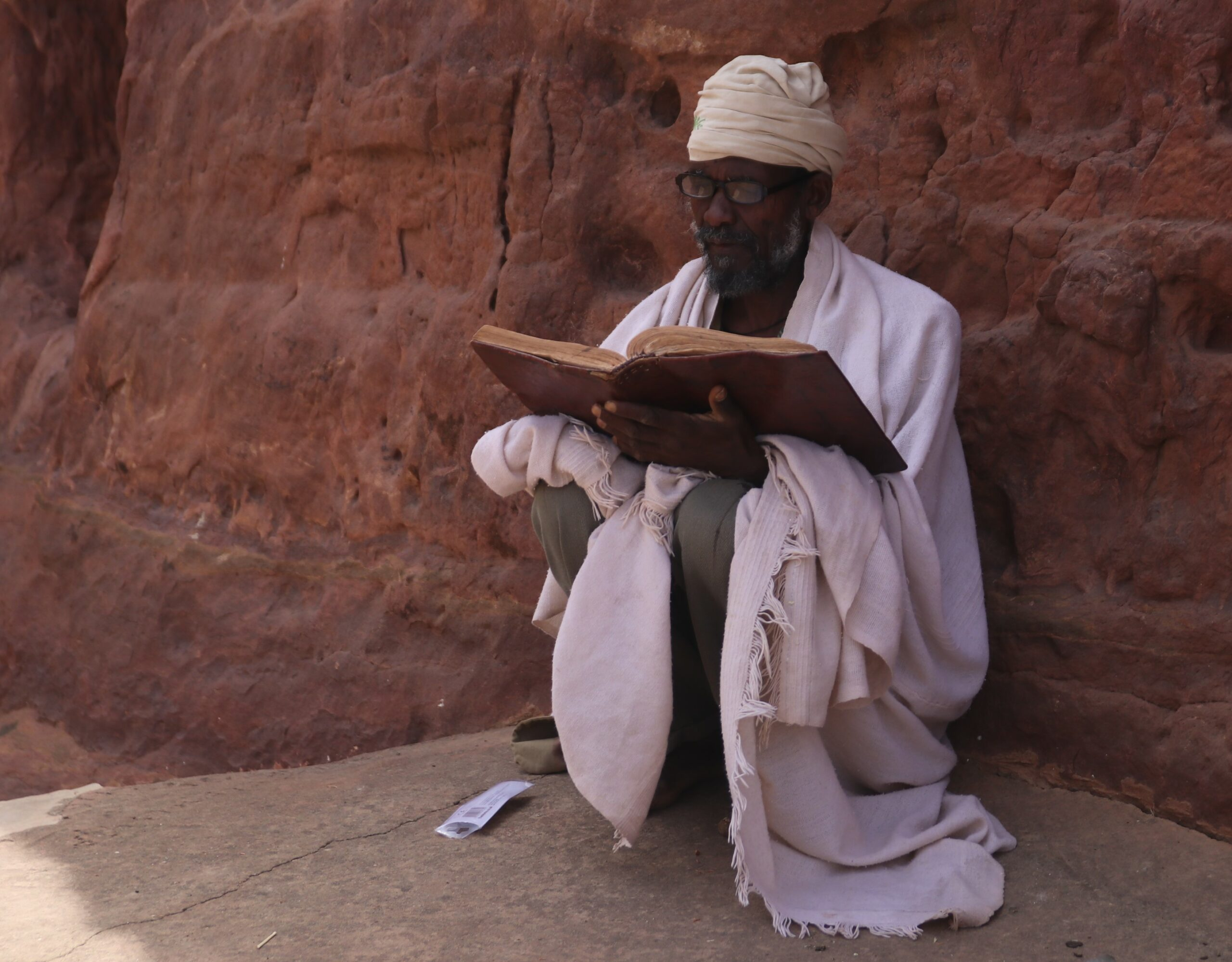 ethiopian man reading outside of a rock church
