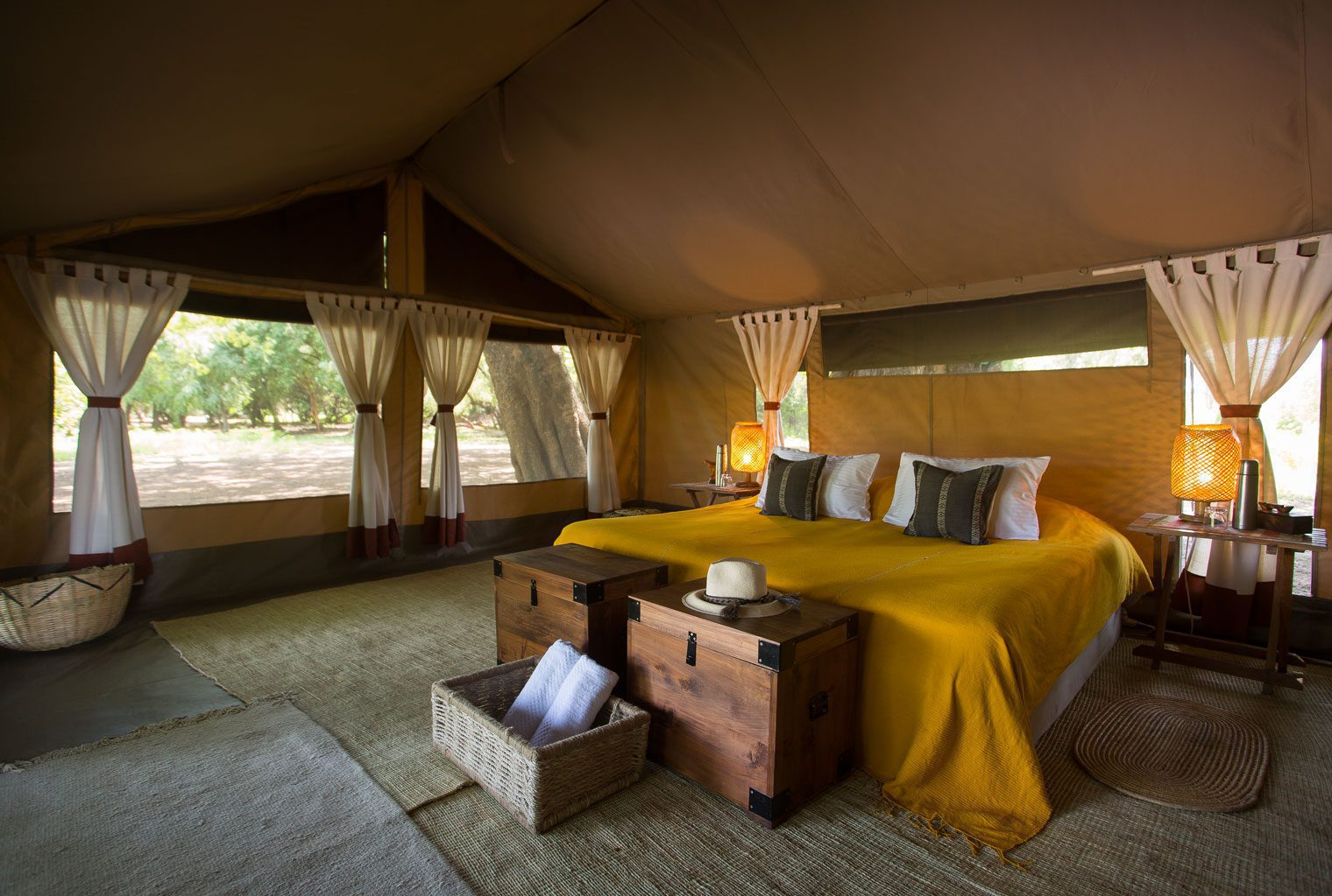 interior view of Lales camp canvas tent with yellow bedspread in the omo valley