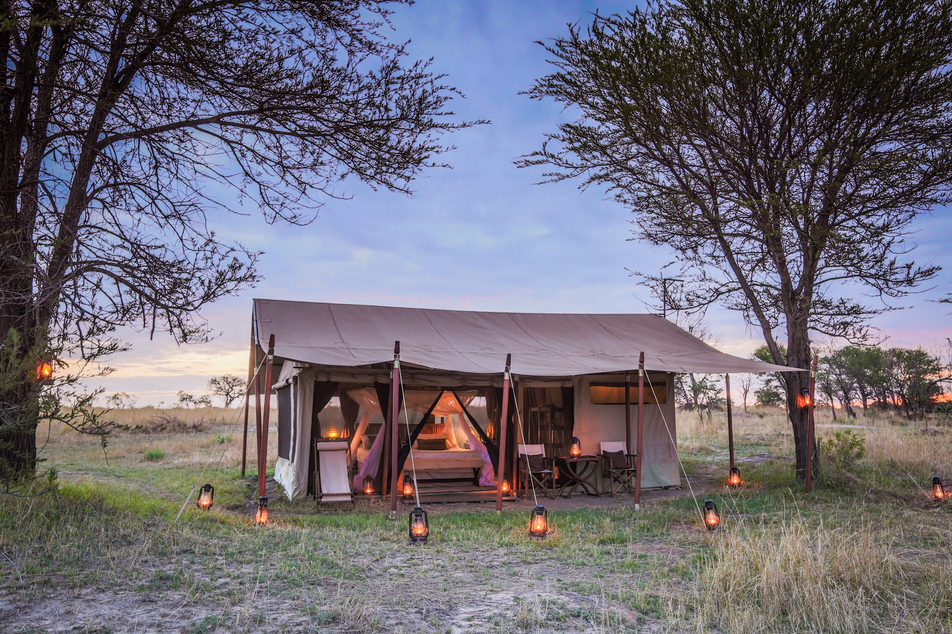 mobile tented camp in the Serengeti surrounded by lit lanterns during tanzania safari