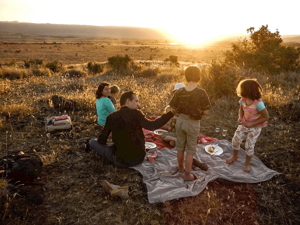 a young family on our premier Kenya safari picnics on a hill overlooking Lewa Wildlife Conservancy while kids play and the sun sets