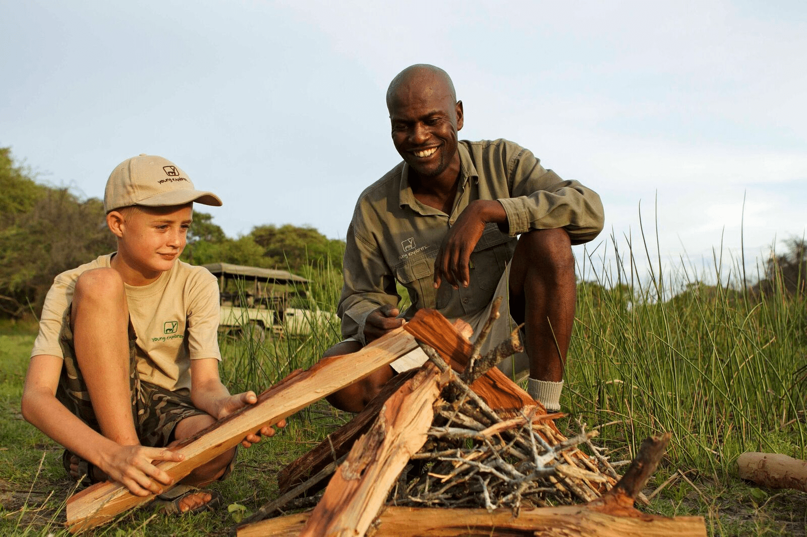 a smiling guide looks on as a young boy builds a fire as part of Footsteps Camp's Young Explorers program on this Southern Africa family safari