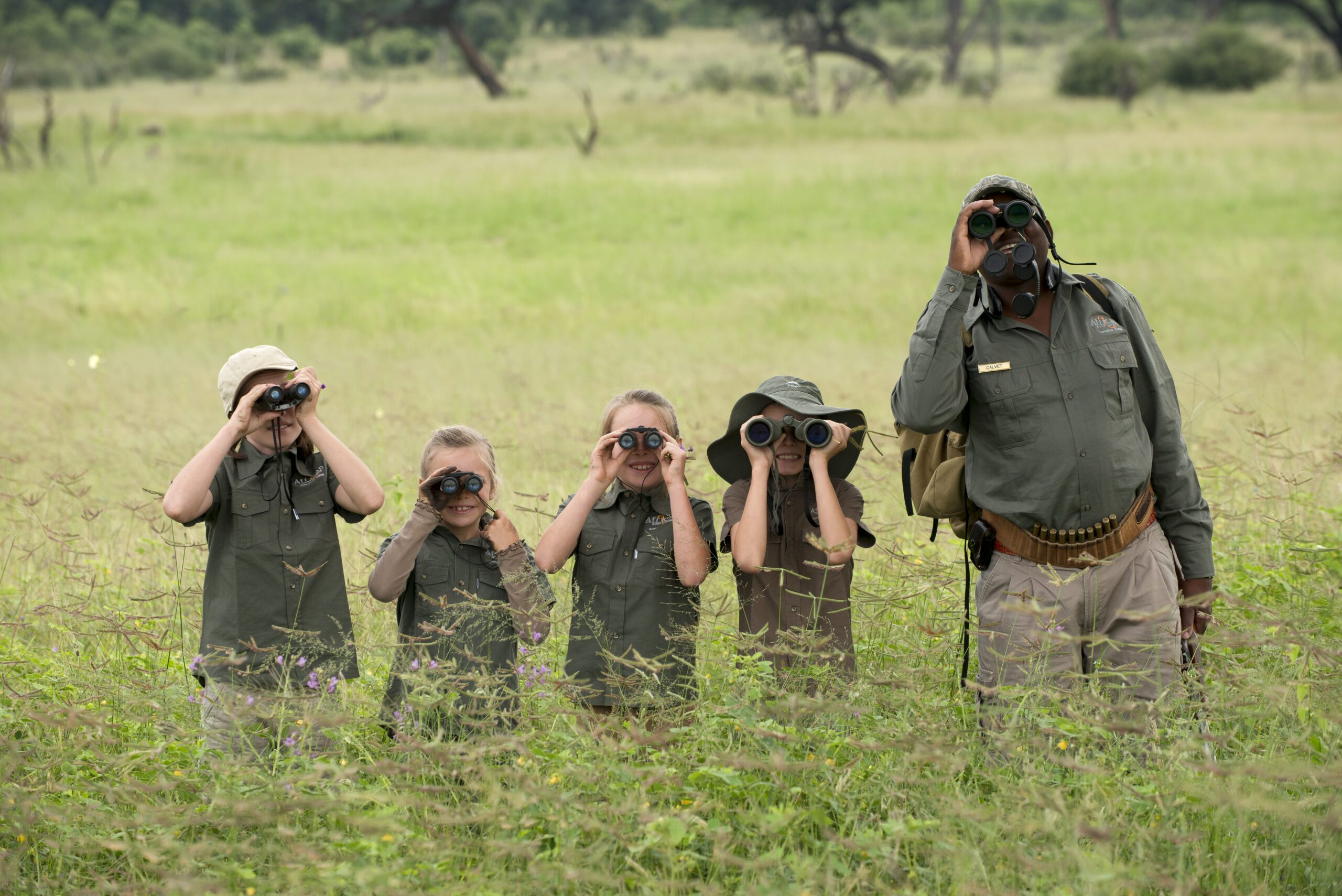 guides and children looking through binoculars on a family safari at African Bushcamps Somalisa