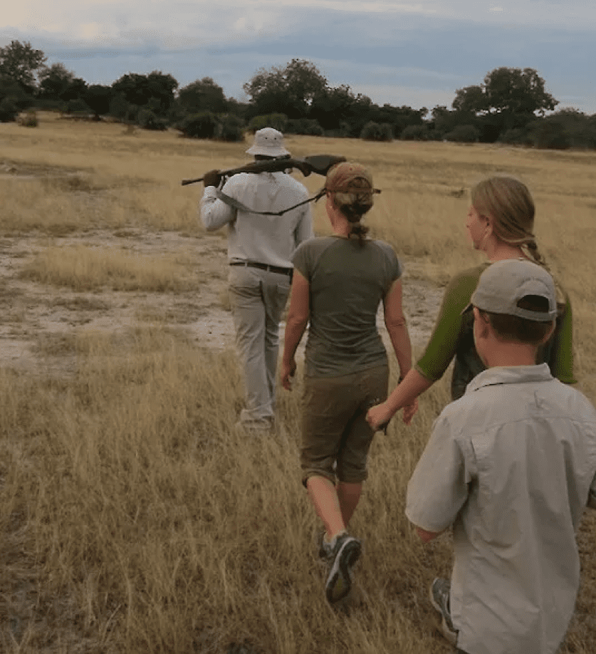 Lara, Elsa, and Graham follow after their guide, Hamadi, on foot during a walking safari. Hamadi carries a rifle for safety.