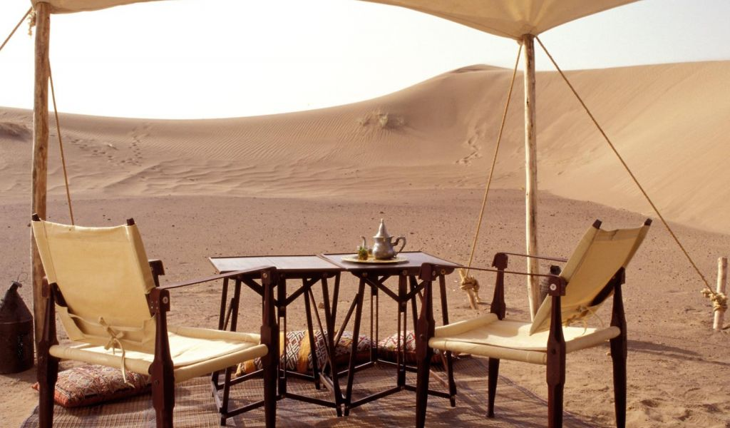 two bistro tables and chairs are set up for tea at a fly camp overlooking sand dunes in the Moroccan desert.