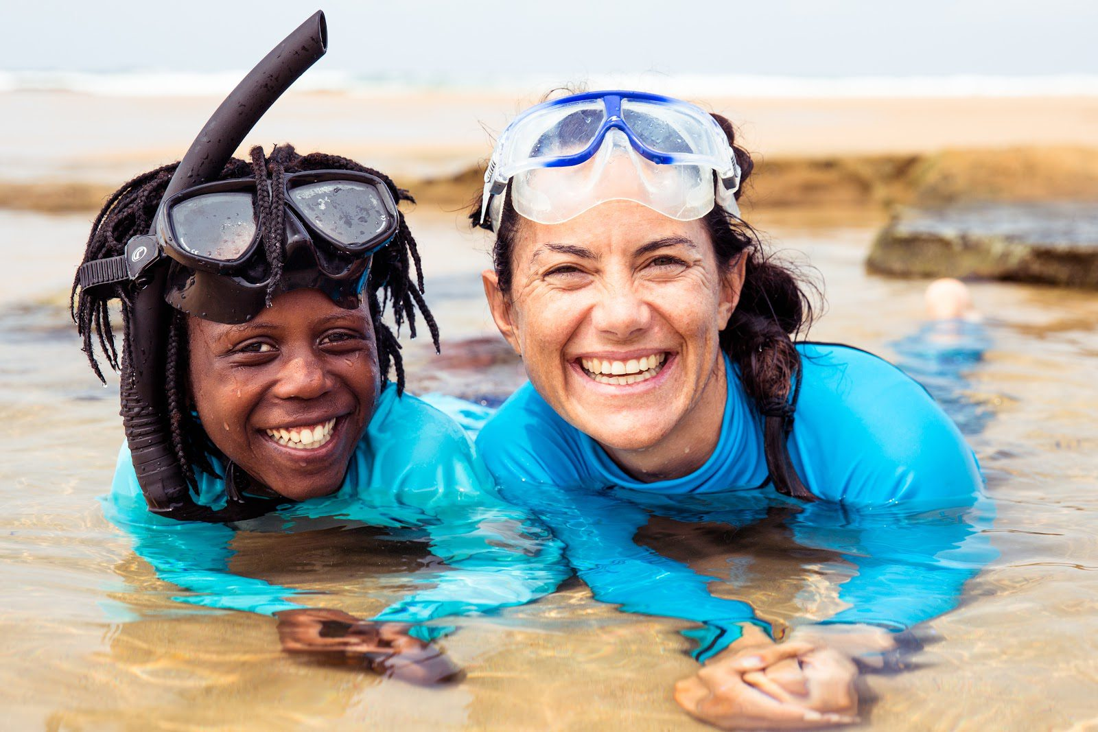 snorkeling on safari is Hanli and a young girl lay in shallow, sandy waters, wearing blue rash guards, googles, & a snorkel