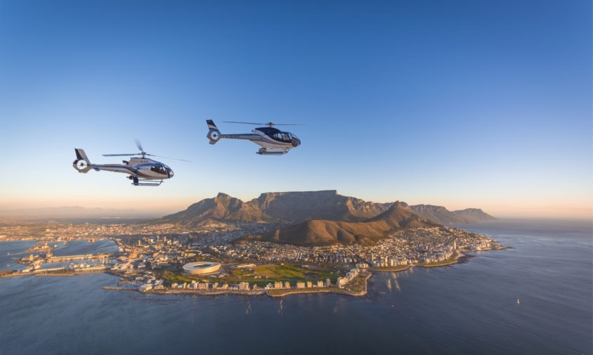 luxury safari in South Africa helicopters flying over the water with cape town backdrop at sunrise