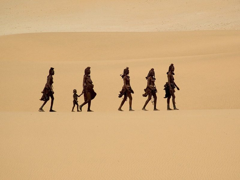 five Himba women and a toddler in traditional dress traverse sand dunes in Northern Namibia. They walk single-file.