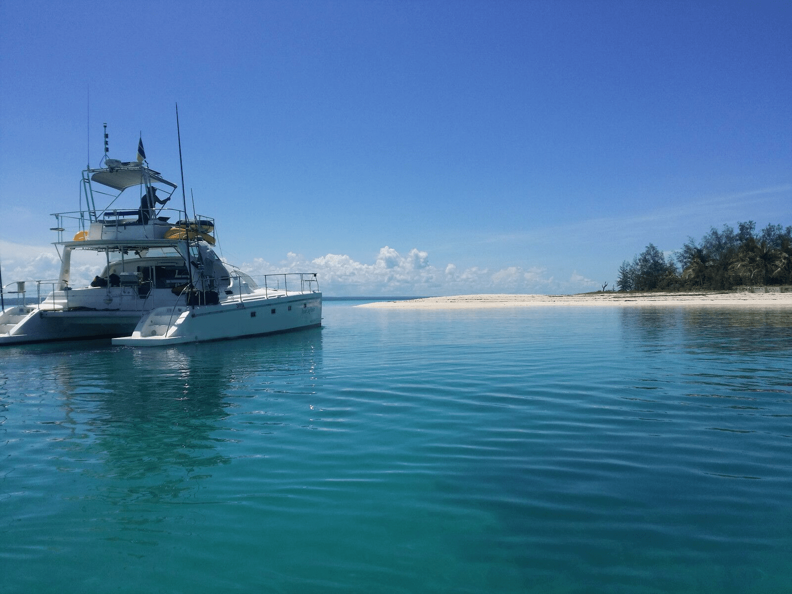 catamaran heading through blue waters to a white sand shore, with blue skies and clouds in the background