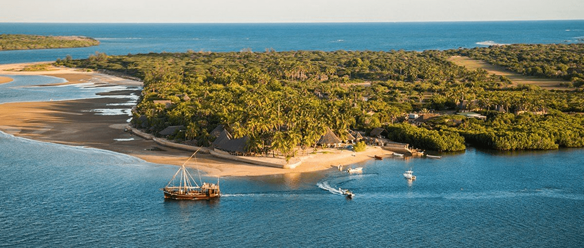aerial shot of a wooden boat and several smaller vessels off a sandy beach in Kenya's Lamu Archipelago. The island is covered with lush, tropical trees and plants.