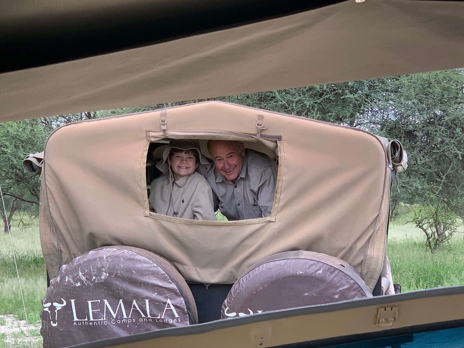 a young boy and his grandpa peer out the back window of a canvas-topped game drive vehicle, grinning