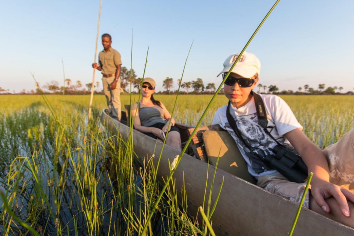 A guide stands in the back of a Mokoro boat, pushing a mother and her son through the grassy waters of the Okavango Delta on mokoro safari