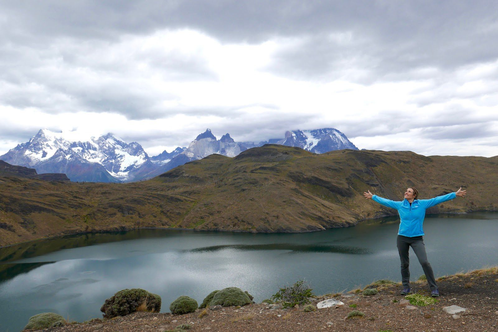 a woman in a blue jacket stretches her arms wide before jagged snow-capped mountains, rugged hills, and a massive lake