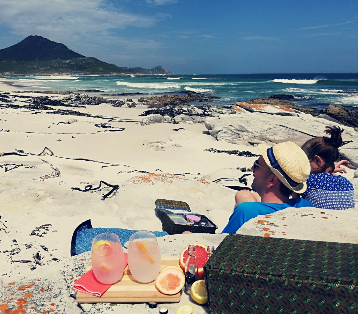 a man in a straw fedora and a woman lounge on a white sand beach with cocktails, blue seas, and Cape Point on this Africa honeymoon safari