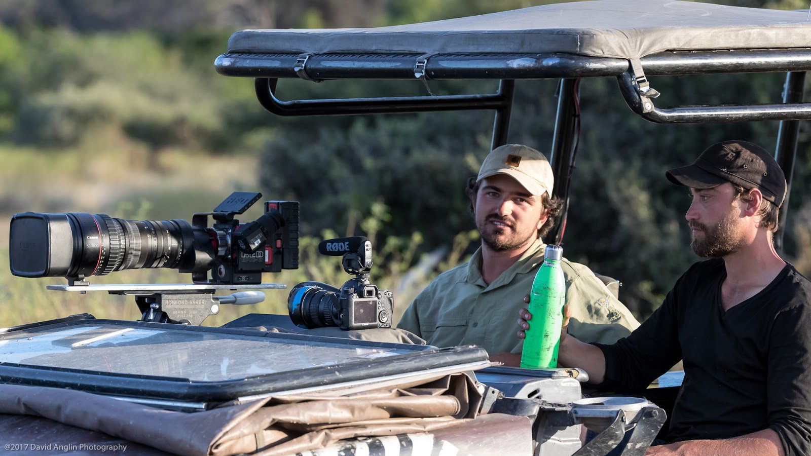 Guided conservation tour featuring a photographer and his guide in a safari vehicle