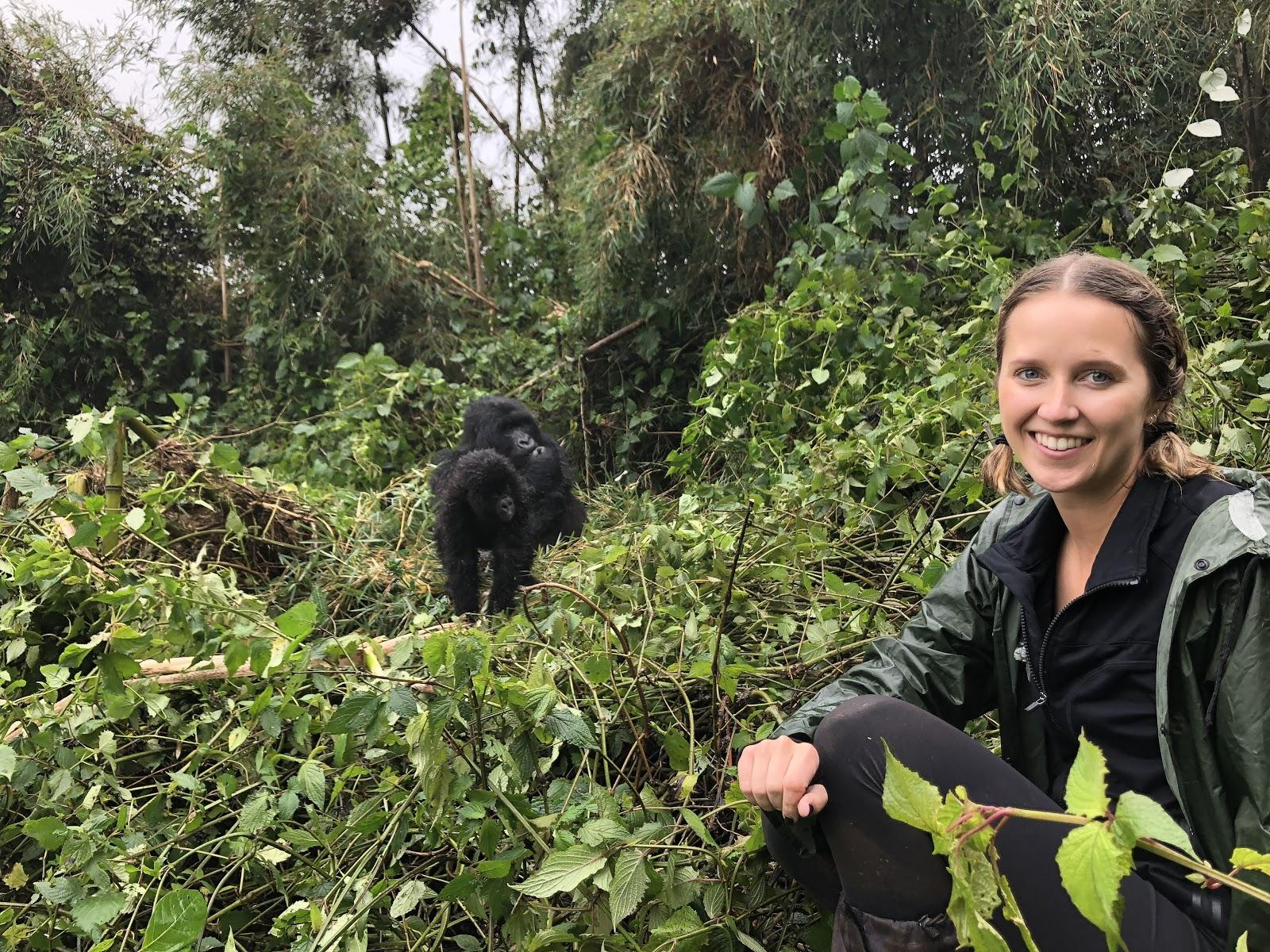 woman sits with gorilla in background