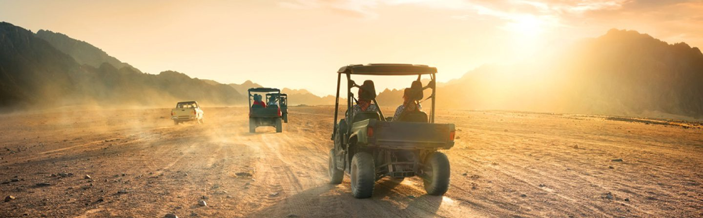 two jeeps on a dusty road at sunset on an atv safari