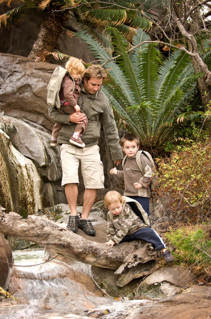 a guide holds one small child as two others climb down the edge of a rocky stream with boulders and ferns behind them
