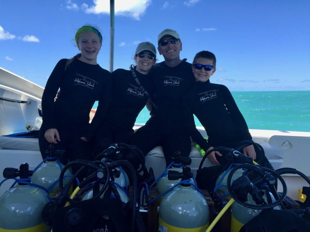 mother, father, daughter, and son all wear wet suits and pose for a photo on their boat amid diving gear and oxygen tanks on family safari