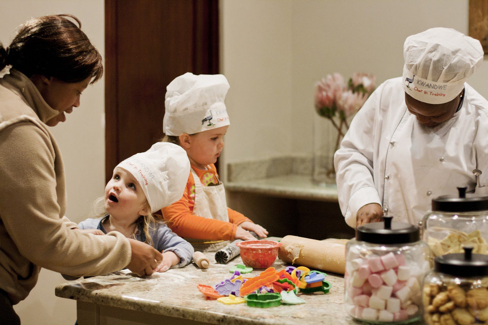 a guide, a chef, and two small girls in chef's hats stand at a kitchen counter strewn with cookie cutters and rolling pins, cooking