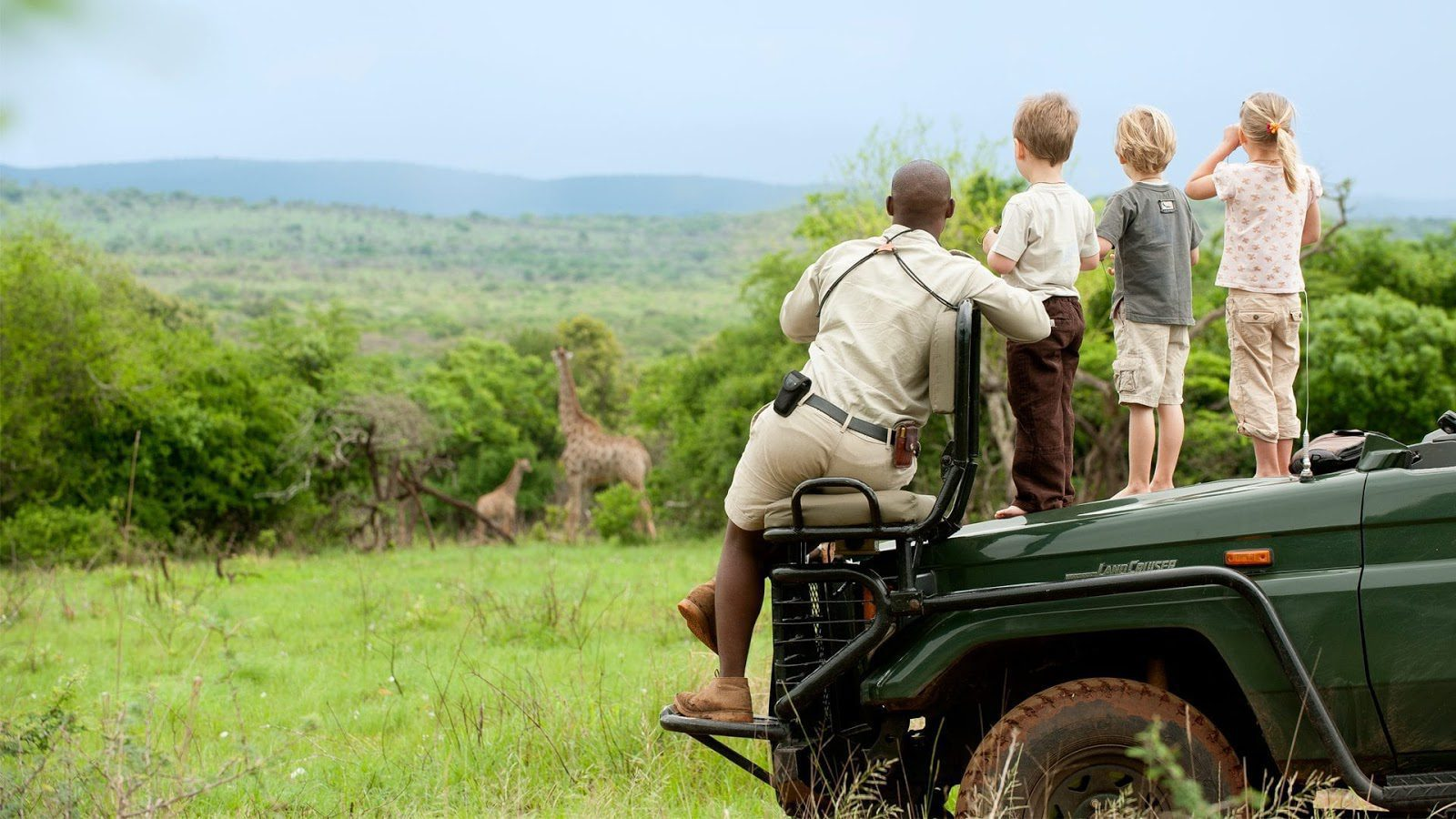 beside their South Africa safari guide, three small children stand atop the hood of a safari vehicle in a green field, watching giraffes