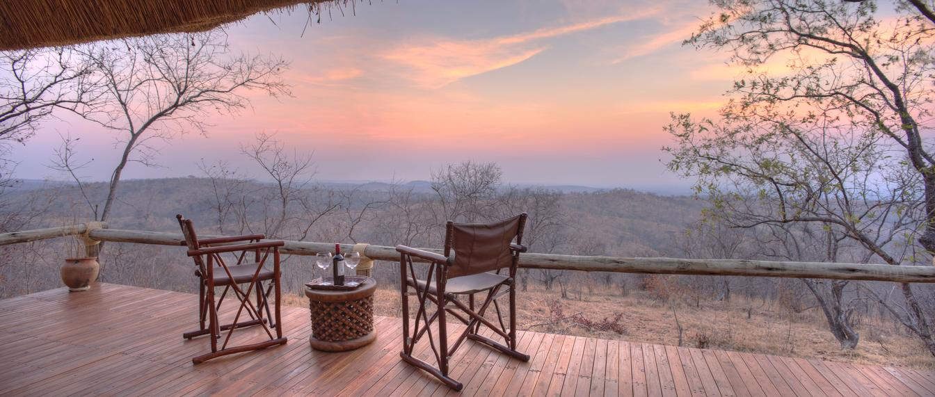 deck with two chairs and trees at sunset seen on Tanzania safari