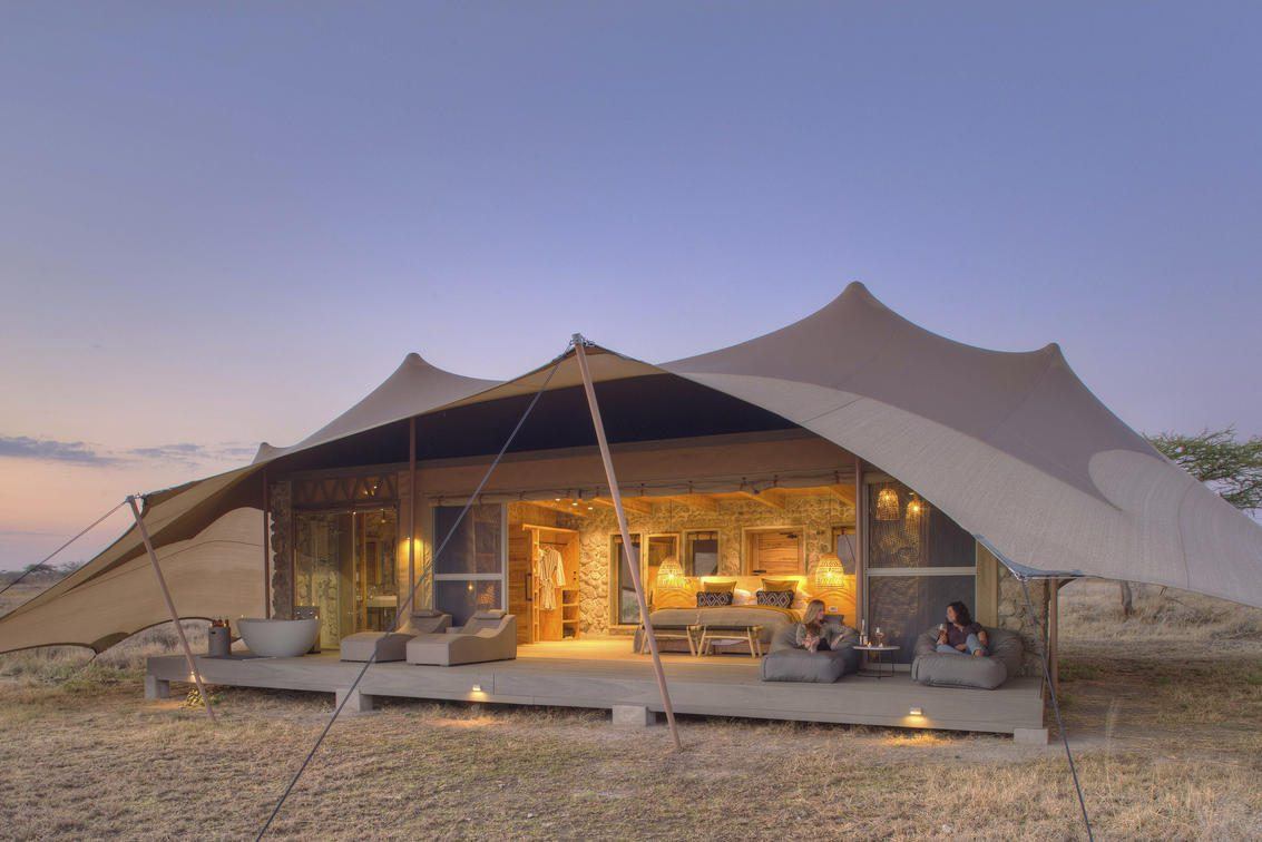 exterior view of a tent at namiri plains lit up at sundown