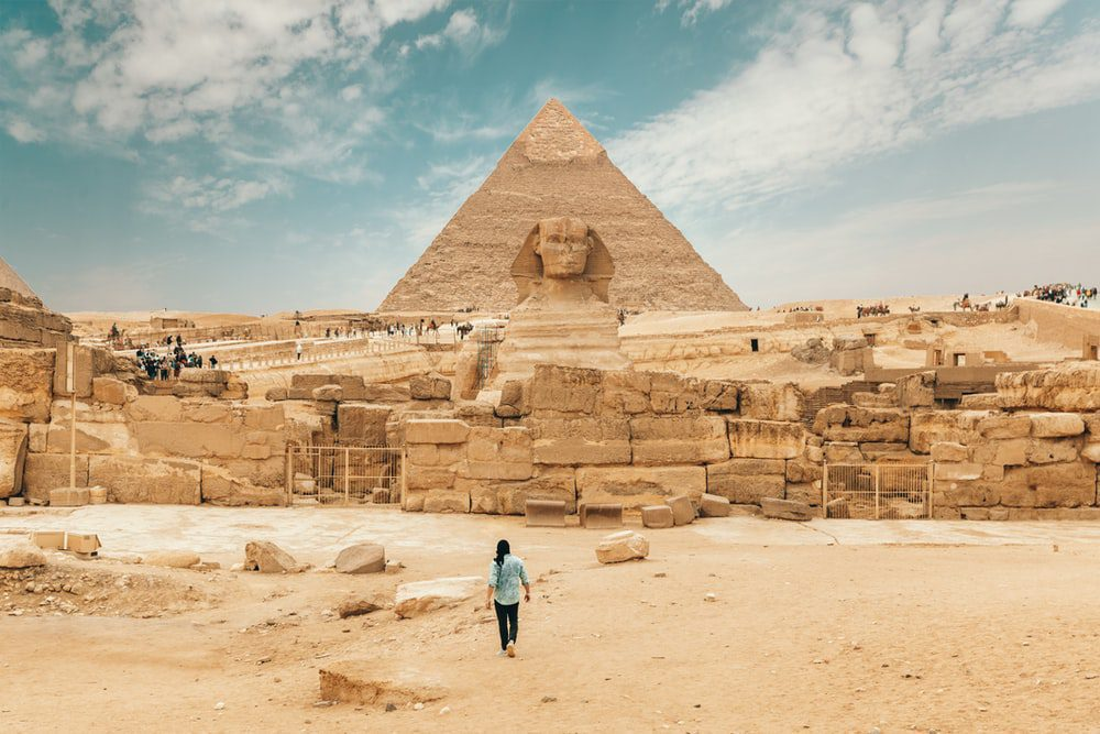 person walking into the pyramids of giza with sphinx in the front