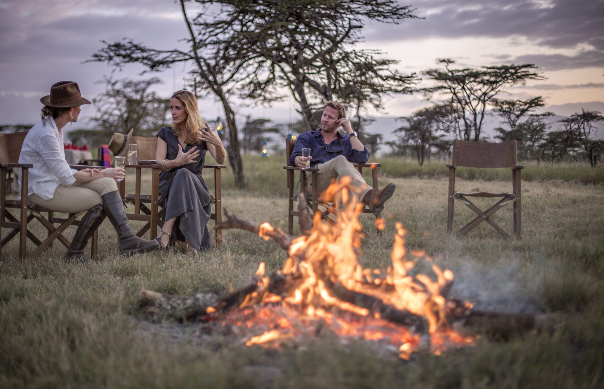 two people sitting in camp chairs around a campfire in the bush at Sirikoi on our premier Kenya safari