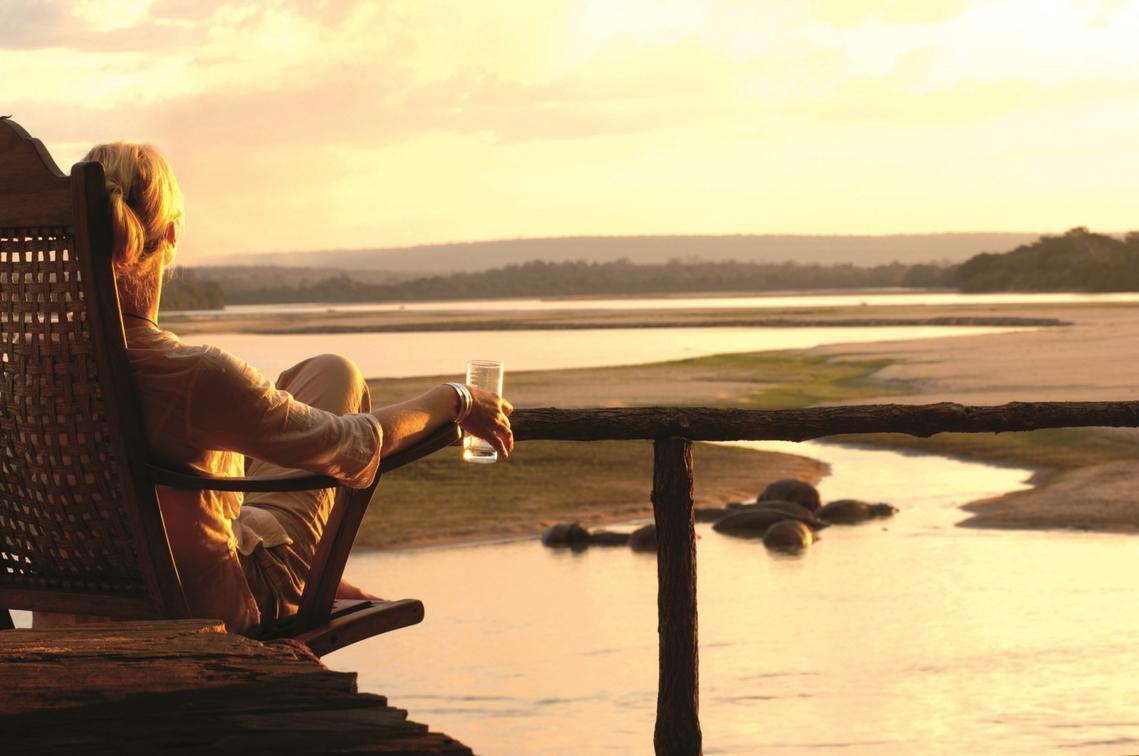 woman enjoying the sunset overlooking the river in the Selous on Tanzania safari