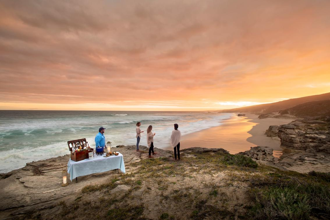 table and drinks set up on rock with ocean views