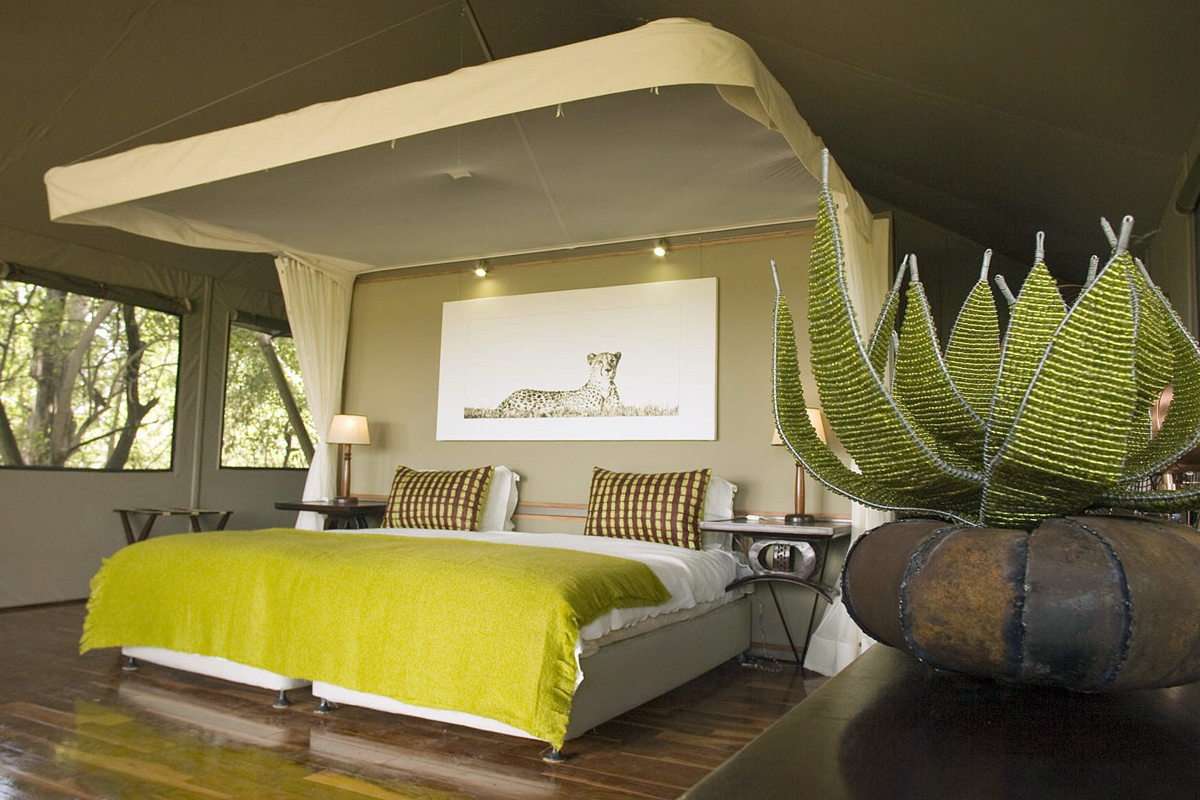 Chitabe Camp interior view of king bed bright chartreuse and cream decor on our off-grid Botswana safari