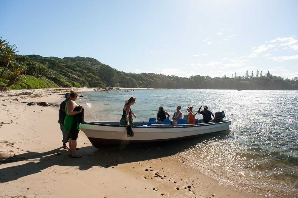 guests getting into a boat on a beach with blue water and green trees on our luxury Madagascar safari