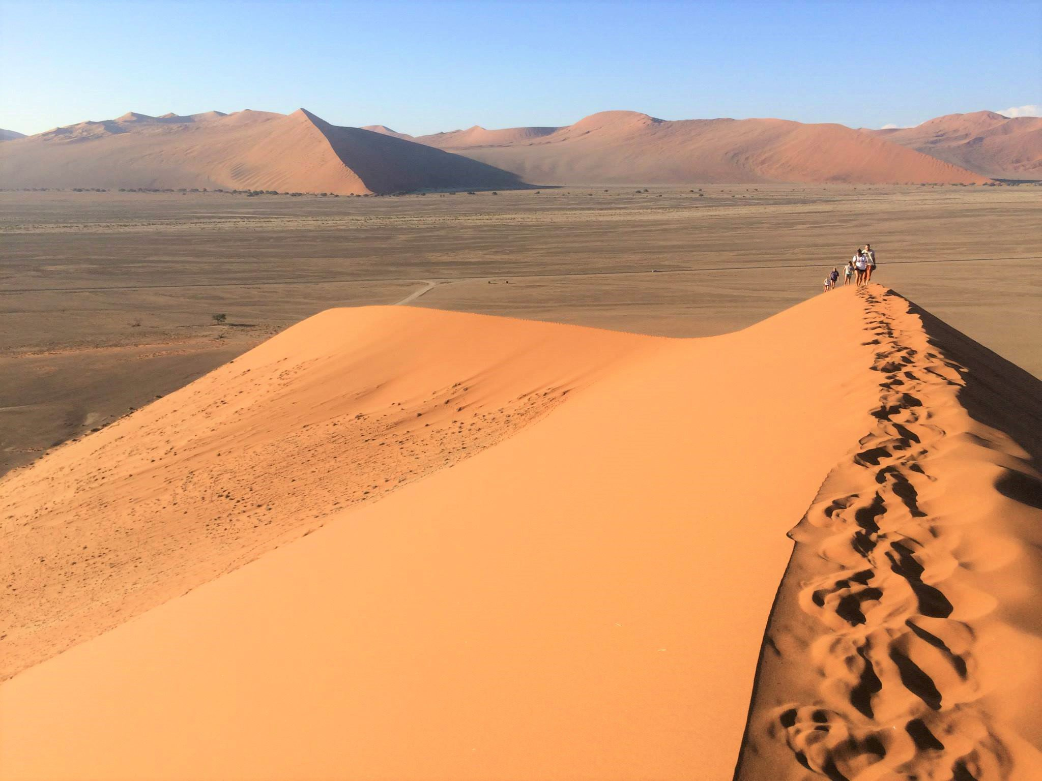 on top of Dune 45 with footprints in the foreground and people walking up in the baackground on our Namibia safari