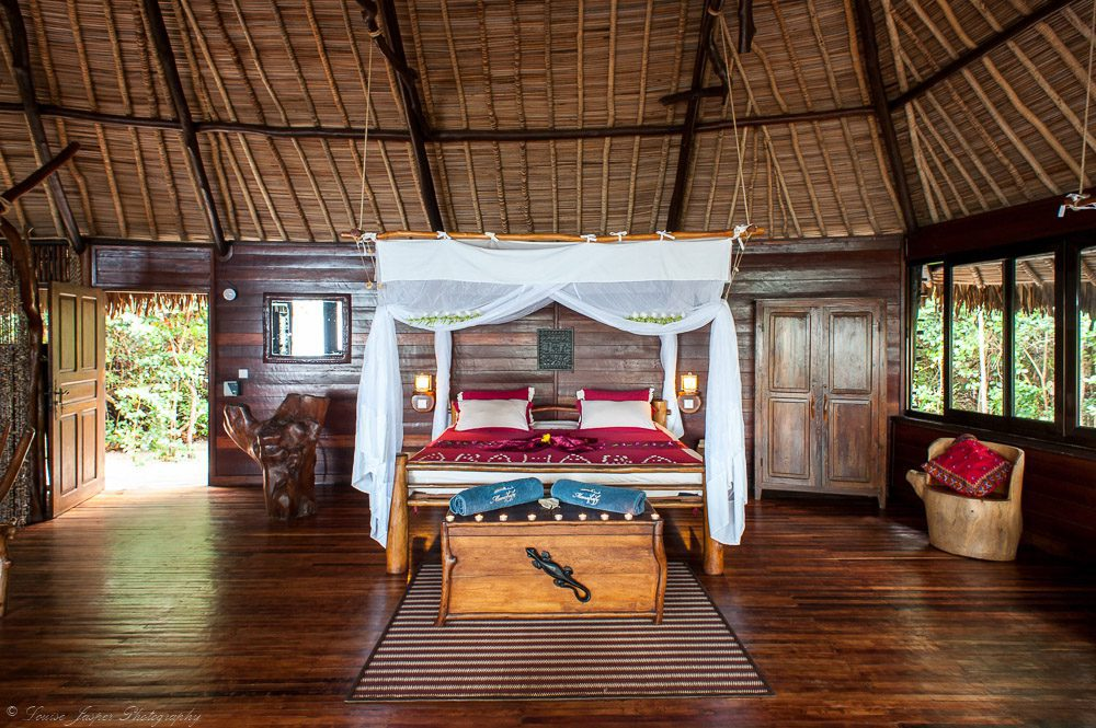 stay here on our luxury Madagascar safari bed with trunk and rug under thatched roof