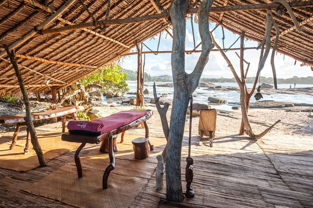 massage table under thatched roof with water in the background