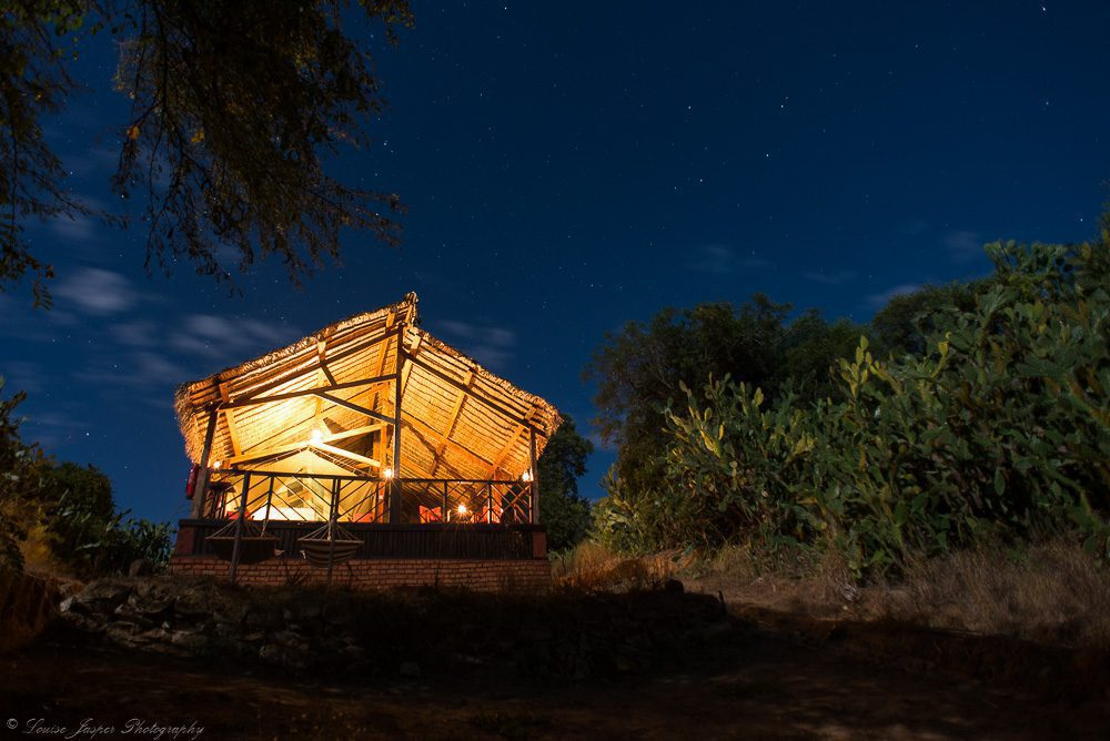 tented structure lit up at night with trees on either side on our luxury Madagascar safari
