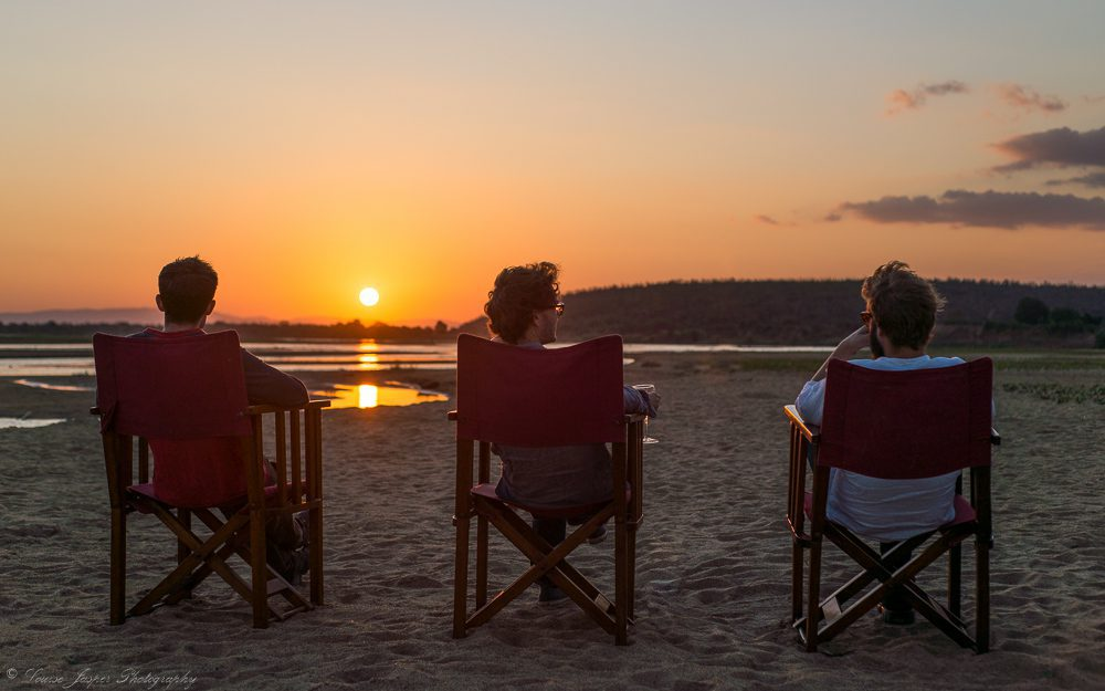 three men sitting in chairs on a beach at sunset on our luxury Madagascar safari
