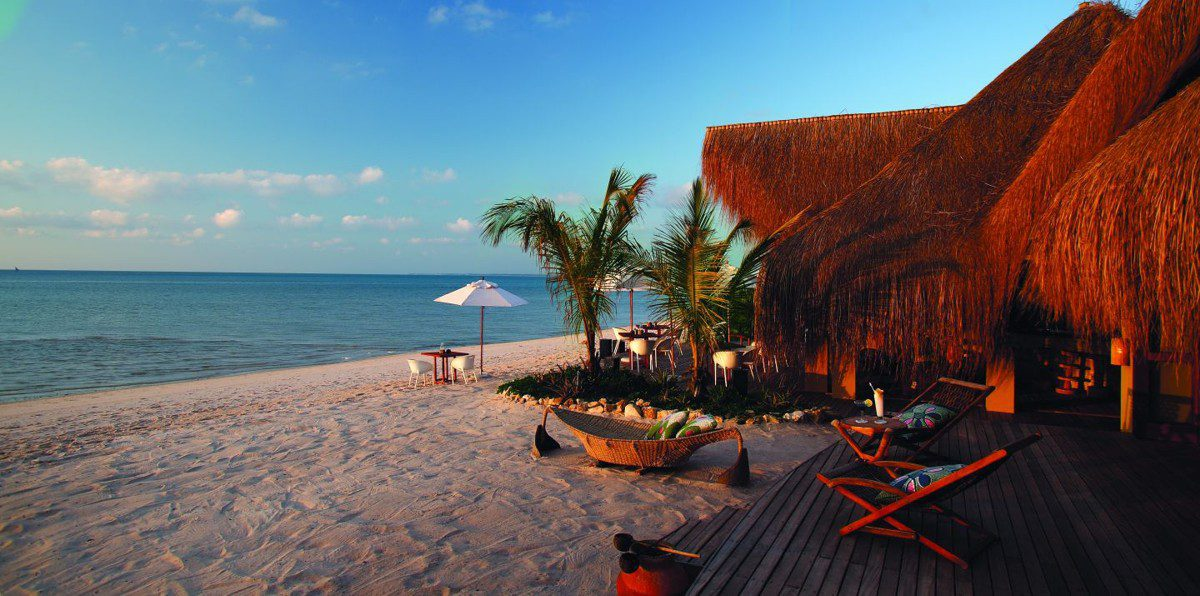 azura main areas featuring a thatched roof, palm trees and views of the indian ocean