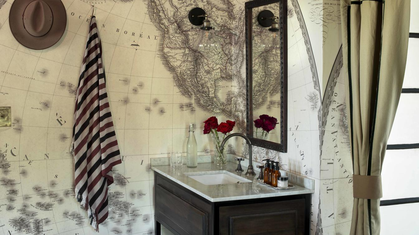map wallpaper and sink with a mirror