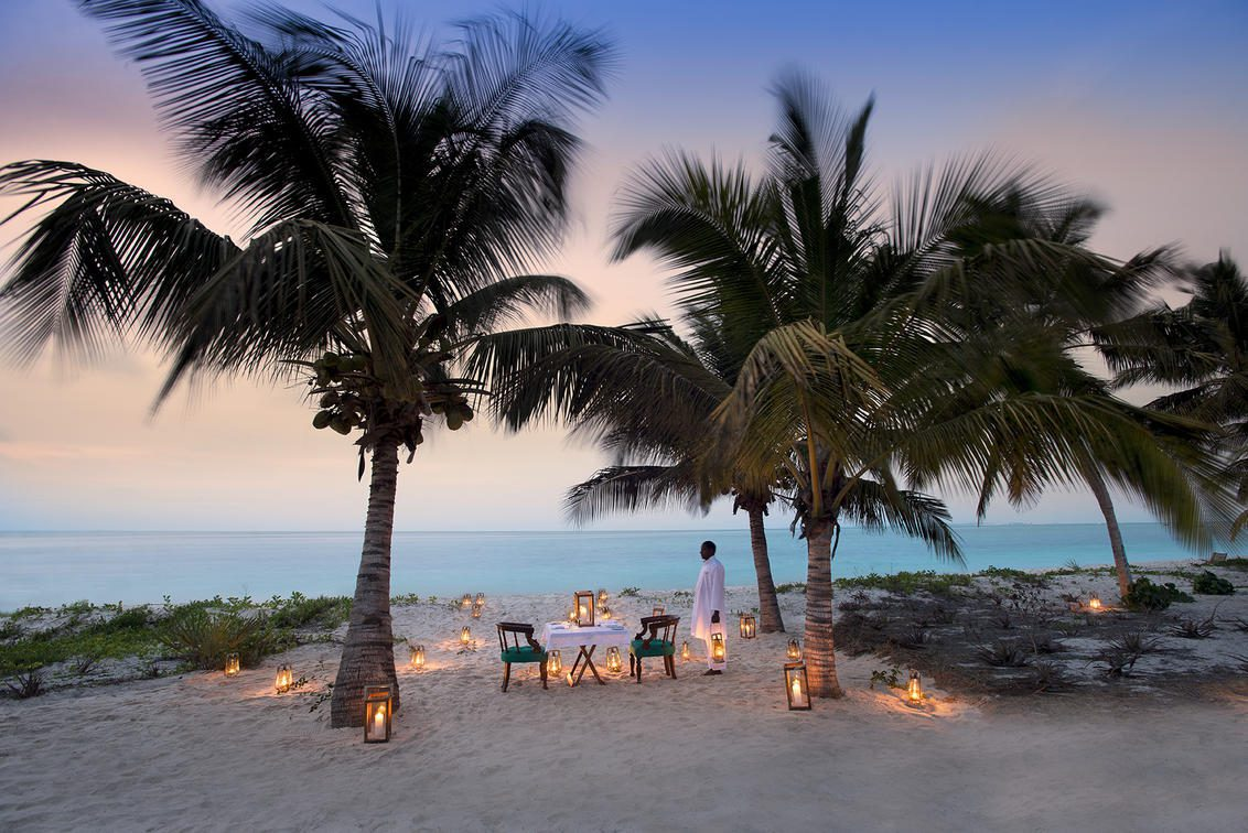 large palm trees on beach with tables set for dinner and lanterns